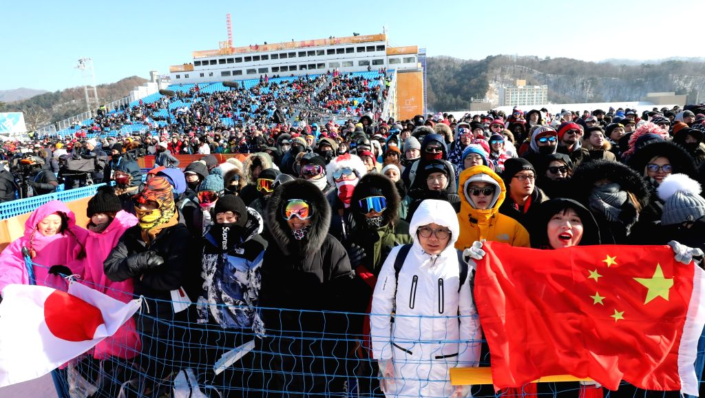 Chinese and Japanese spectators cheer for snowboarders from their respective countries competing at a snowboarding event at Phoenix Snow Park in PyeongChang, Gangwon Province, on Feb. ...