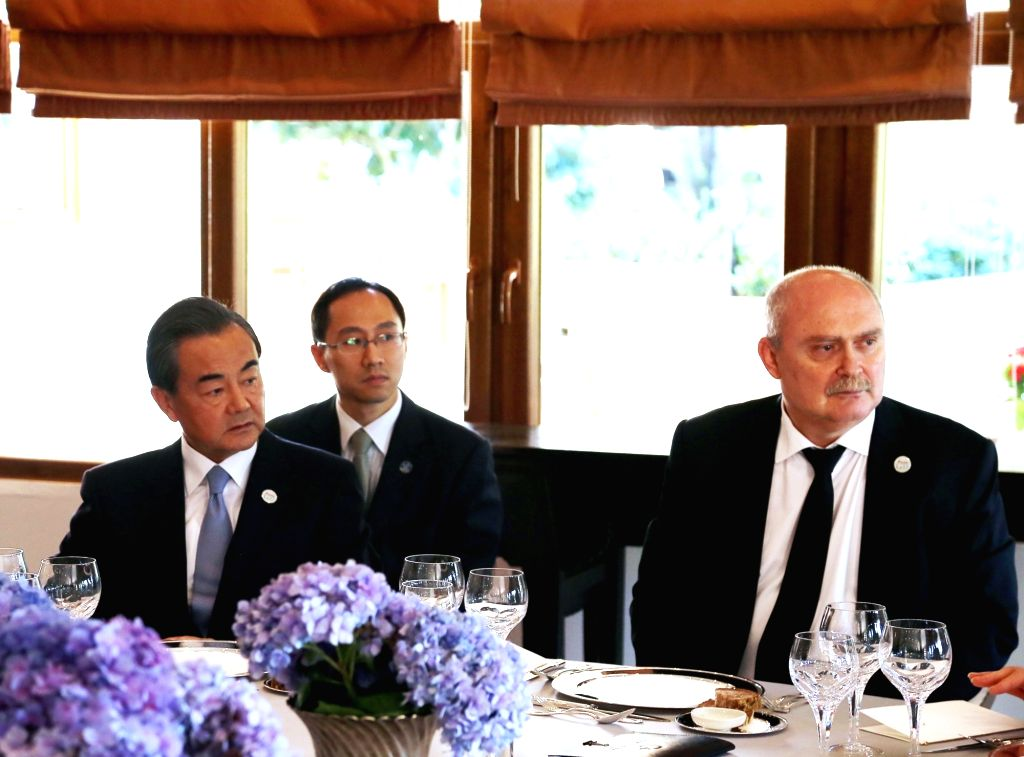 Chinese Foreign Minister Wang Yi (L) and Turkish Foreign Minister Feridun Sinirlioglu (R) attend a working luncheon attended by foreign ministers of the G20 members ... - Wang Y