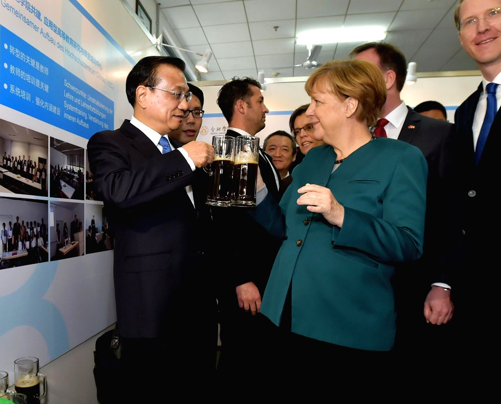 Chinese Premier Li Keqiang (L) and German Chancellor Angela Merkel (C) drink beer brewed by Chinese and German students during their visit to Hefei University in ...