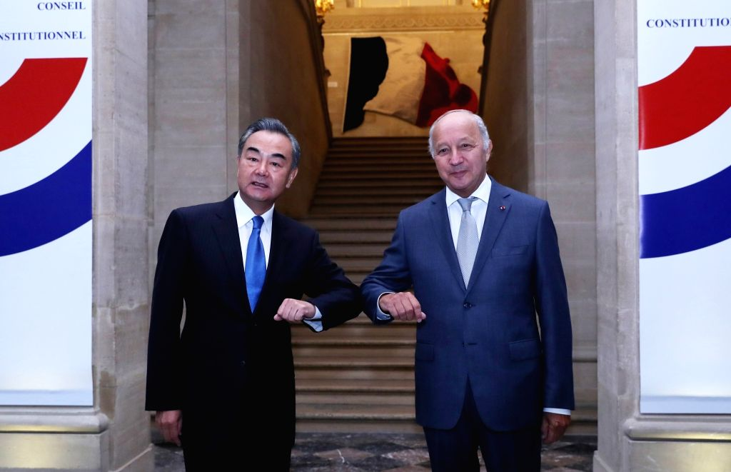 Chinese State Councilor and Foreign Minister Wang Yi (L) touches elbows with Laurent Fabius, president of France's Constitutional Council, in Paris, France, on Aug. ... - Wang Y