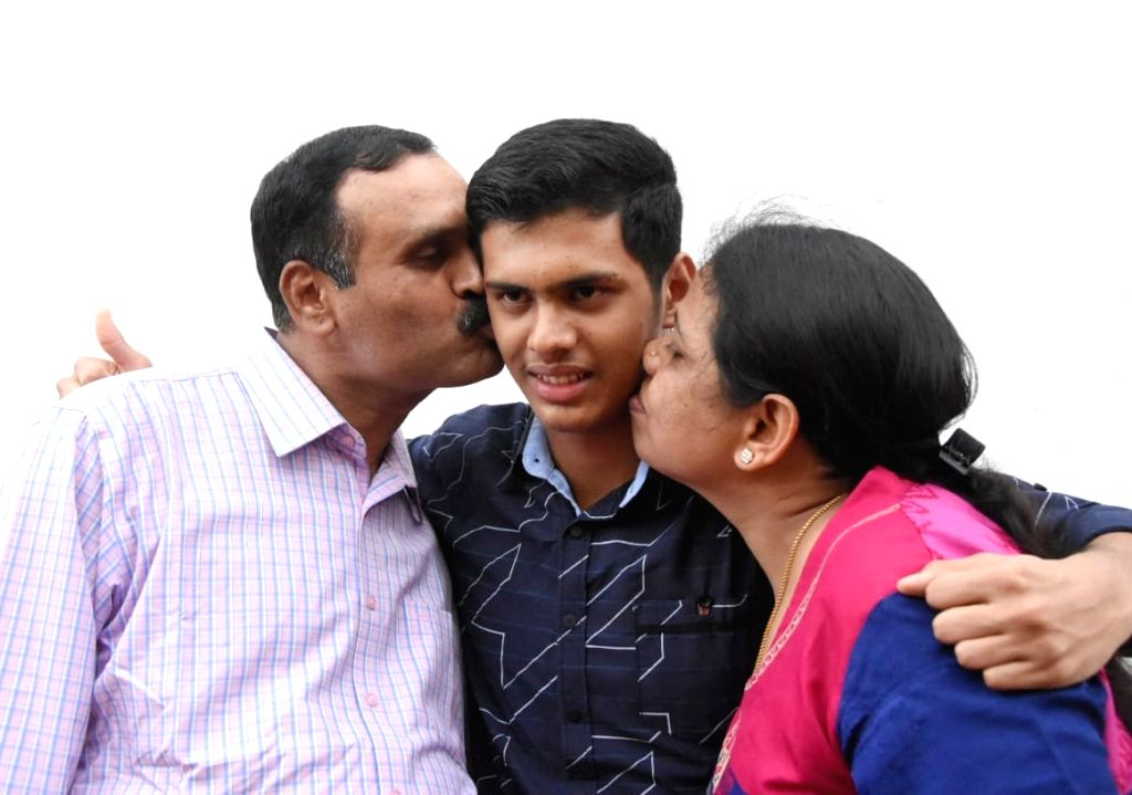 Chirayu KS from St. Mary's High School celebrates with his parents after he topped the Karnataka Secondary School Leaving Certificate (SSLC) board examinations as the results were ...