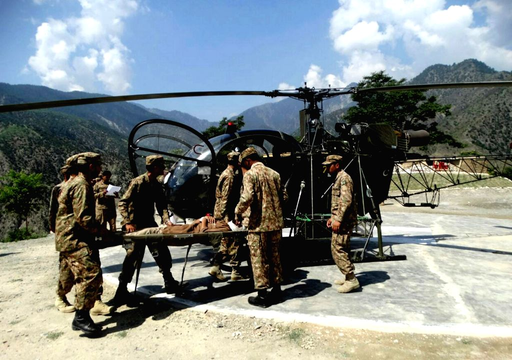 CHITRAL, July 3, 2016 - Photo released by Pakistan's Inter Service Public Relations (ISPR) on July 3, 2016 shows Pakistani soldiers transfer an injured survivor to a helicopter in Chitral, northwest ...