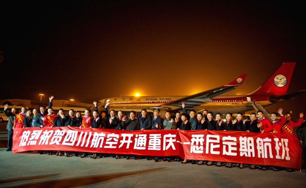 Staff members and honored guests pose for a group picture before a Sichuan Airlines A330 passenger plane, the first one for the direct air route linking western ..