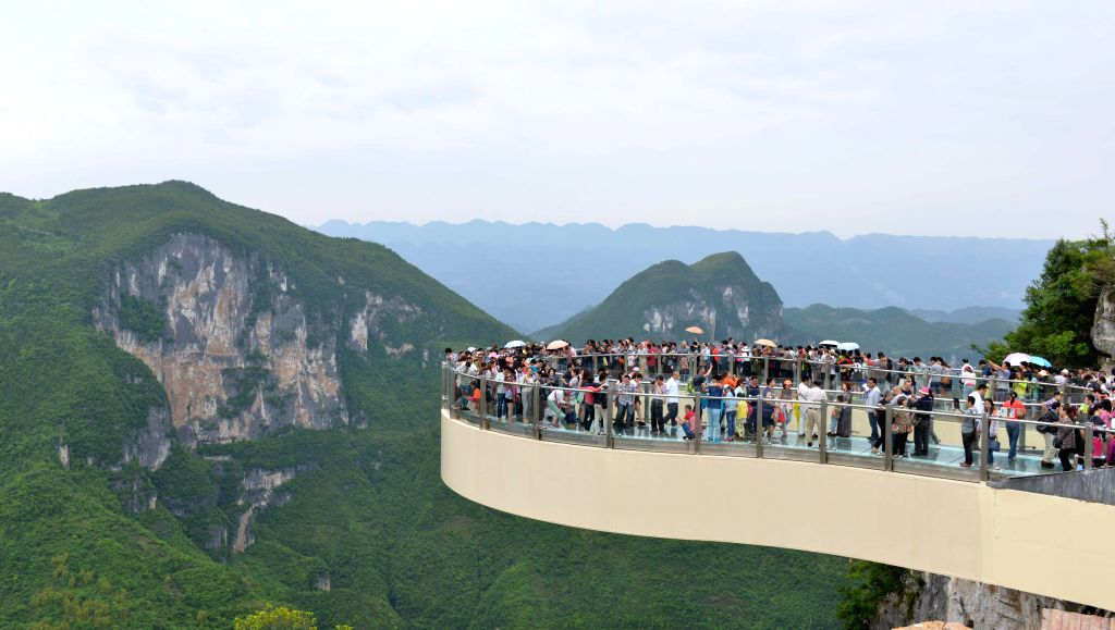 Tourists go sightseeing on a transparent horseshoe-shaped cantilever bridge at the Yunyang Longgang Geological Park in Chongqing, southwest China, May 3, 2015.  The ...