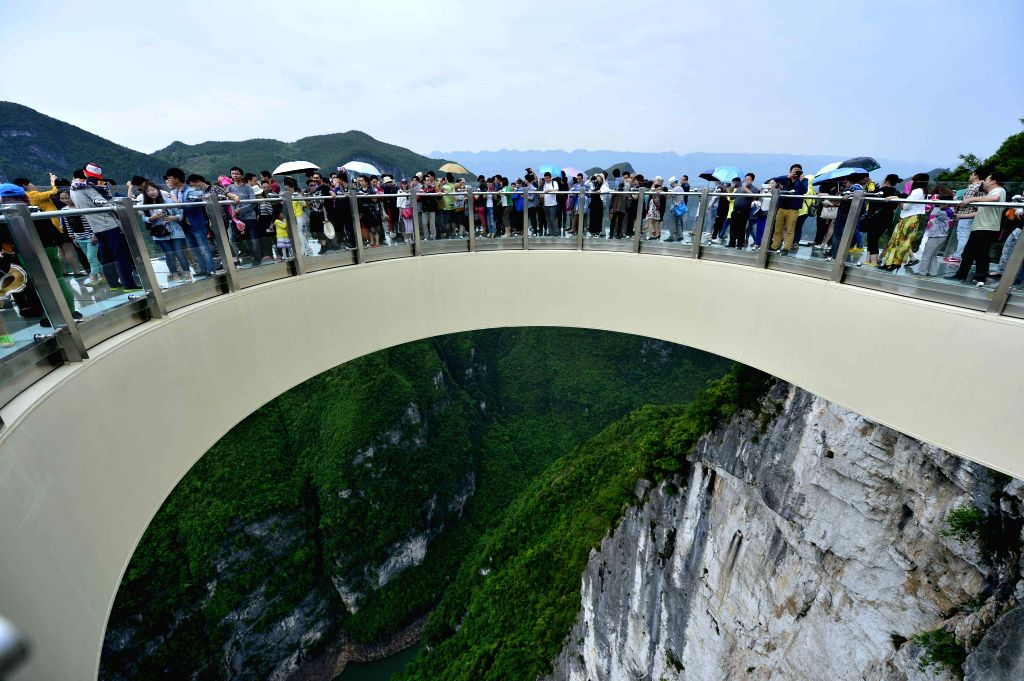 Tourists go sightseeing on a transparent horseshoe-sahped cantilever bridge at the Yunyang Longgang Geological Park in Chongqing, southwest China, May 3, 2015.  The ...