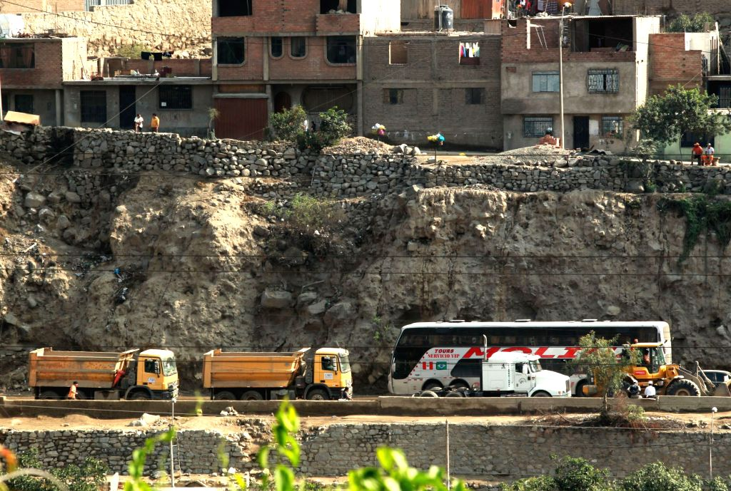 A bus moves through a recently opened lane of the Central Highway, after the landslides in Chosica district of Lima, Peru, March 27, 2015. At least nine people ...