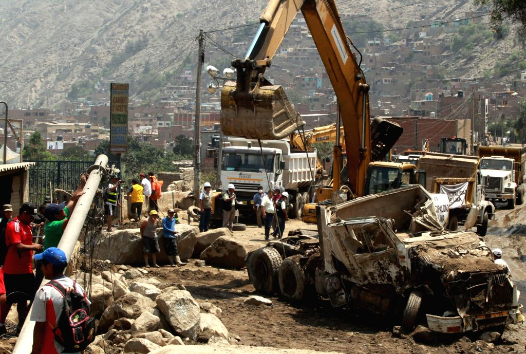 People clear up the blocked road after the landslides in Chosica district of Lima, Peru, March 27, 2015. At least nine people were killed and four others were ...