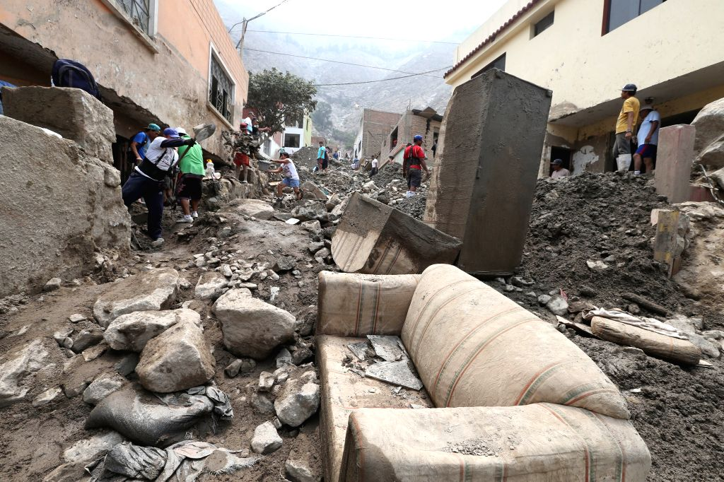 Workers take part in the cleaning of the Central Highway after a landslides in Chosica district of Lima, Peru, on March 29, 2015. At least nine people were killed ...
