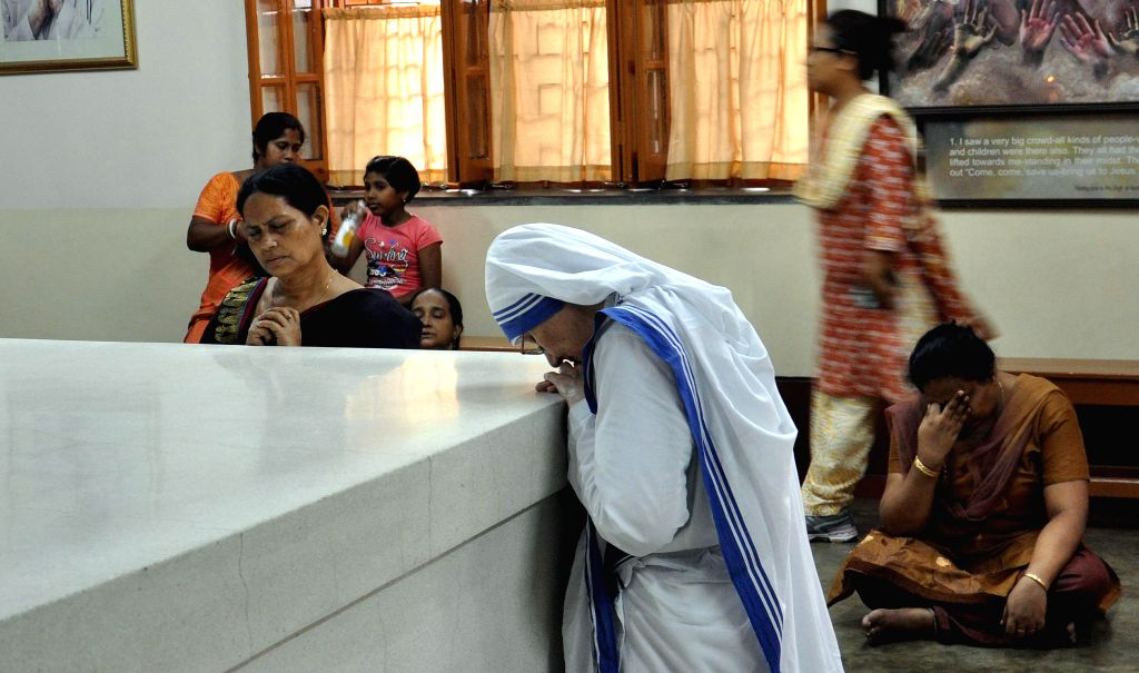 Christians offer prayers at the tomb of Mother Teresa on Good Friday at The Mother House in Kolkata on April 18, 2014.