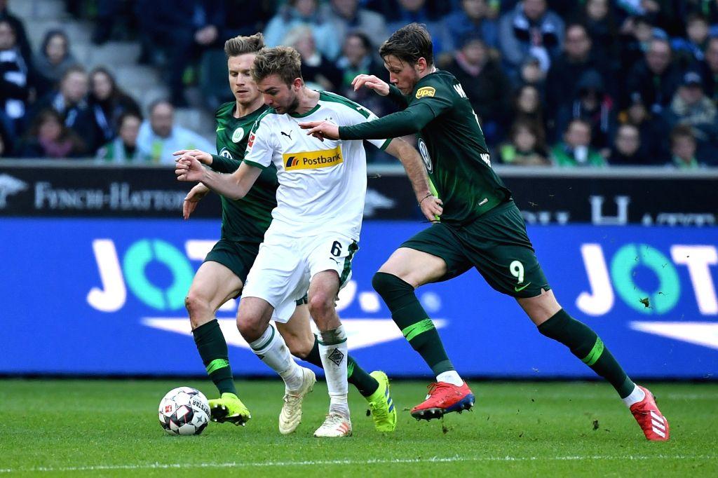 Christoph Kramer (C) of Moenchengladbach vies with Yannick Gerhardt (L) and Wout Weghorst of Wolfsburg during the Bundesliga match between Borussia ...