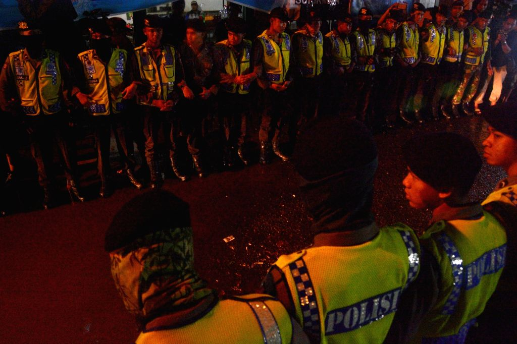 CILACAP, July 29, 2016 - Police officers stand guard when an ambulance carrying the body of an executed prisoner leaves the port of Nusa Kambangan prison island, in Cilacap, Central Java, Indonesia, ...
