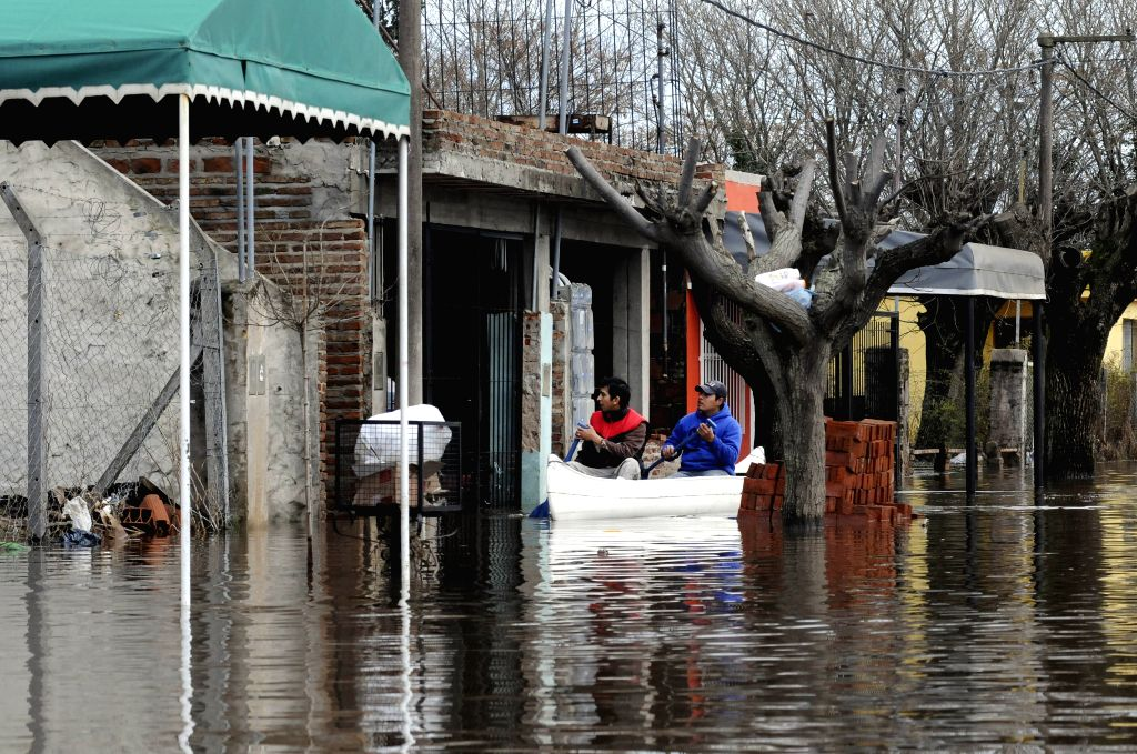 Citizens row a boat in a flooded street in the city of Arrecifes, in Buenos Aires, Argentina, on Aug. 11, 2015. According to the local press, at least 380 ...