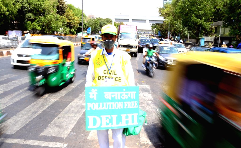 Civil Defence volunteers stand on Delhi streets with placards urging people to follow odd-even traffic scheme aimed at battling pollution on April 18, 2016.