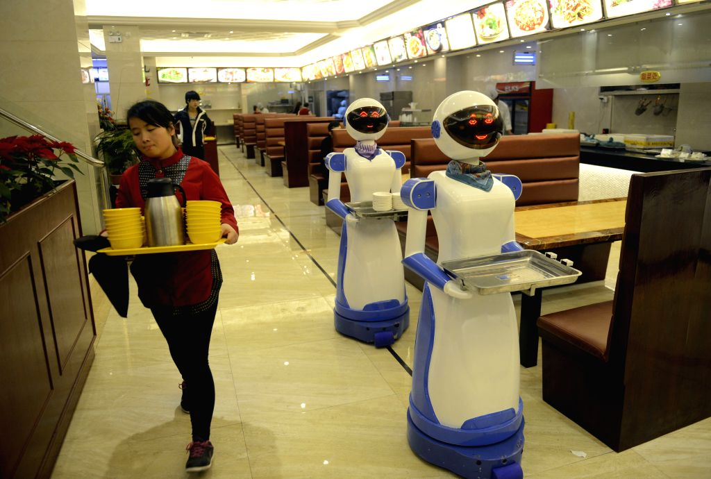 Cixi (China): A waitress passes two server robots at a restaurant in Cixi, east China's Zhejiang Province, Nov. 27, 2014. A newly opened restaurant in Cixi has introduced two server robots which can .