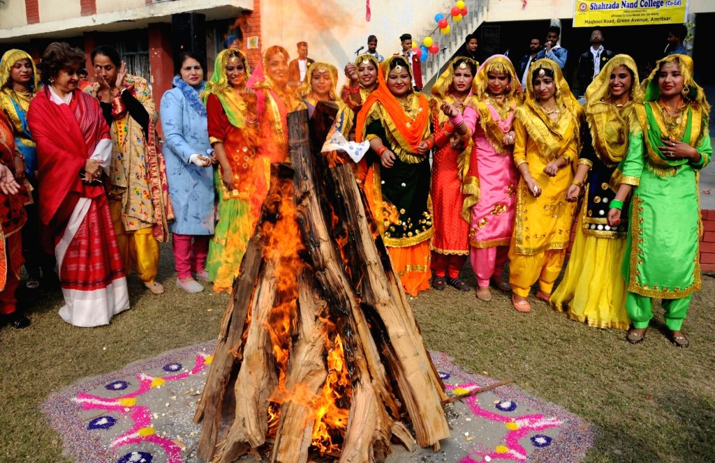 College students dressed up in traditional attires celebrate Lohri on the eve of the festival in Amritsar, on Jan 12, 2019.