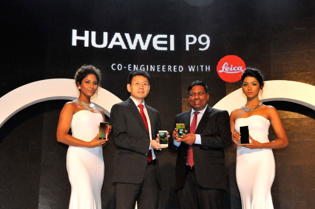 COLOMBO, June 25, 2016 - Wang Shunli (2nd L), CEO of Huawei Sri Lanka, hands over the P9 smartphone to Asoka (2nd R), CEO of Huawei's local exclusive selling agency Singer Group, at the launch ...