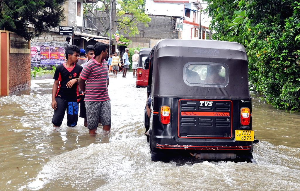 COLOMBO, May 16, 2016 - People walk on the road which was cut off from minor floods in Colombo, Sri Lanka, May 16, 2016. Several roads in the country have been cut off from minor floods and fallen ...