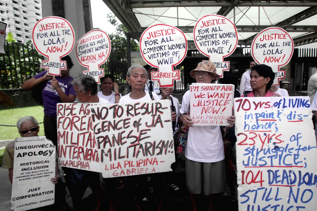 """Comfort woman"""" survivors hold placards during a protest rally in front of the Japanese Embassy in Pasay City, the Philippines, Aug. 14, 2015. Former ..."""