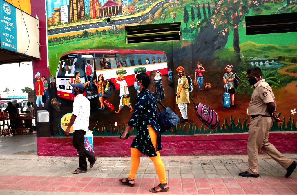 Commuters arrive at a bus stand to board buses to reach their respective destinations, in Bengaluru on July 11, 2020.