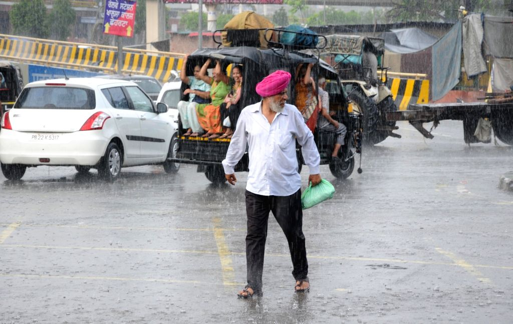 Commuters during rains, in Amritsar on Aug 12, 2018.
