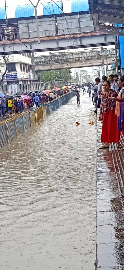 Commuters trudge flooded railway tracks after sunurban trains of Western Railway were paralysed in Mumbai on Sep 4, 2019. The Western Railway (WR) had to suspended suburban and long distance ...