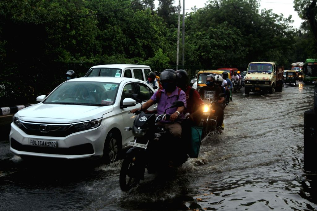 Commuters wade through the water-logged Sri Aurobindo Marg after rains in New Delhi on Aug 1, 2020.