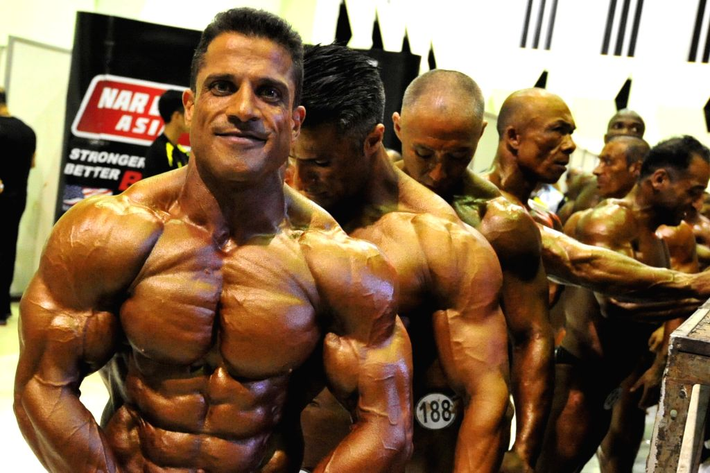 Competitors warm up backstage during World Bodybuilding and Physique Sports Championship 2015 in Bangkok, Thailand, Nov. 27, 2015. The three-day competition ...