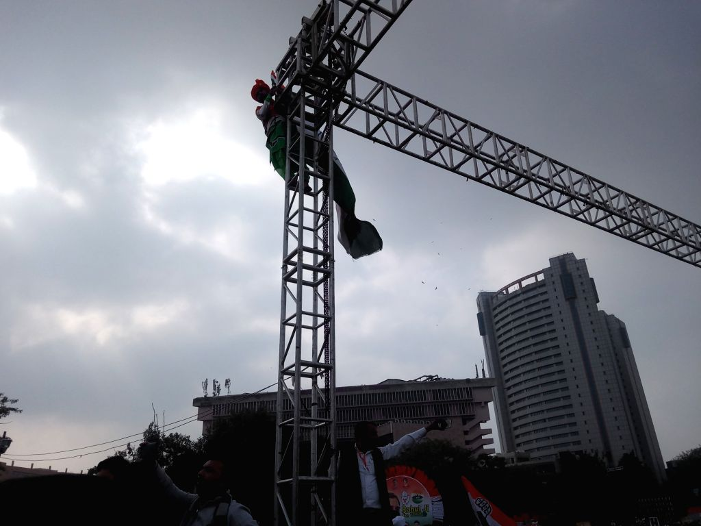 Congress activists climb on the LED video stand, that was placed at the Ramlila maidan to give videos of their leaders speaking from the stage, during 'Bharat Bachao' Rally organised by ...