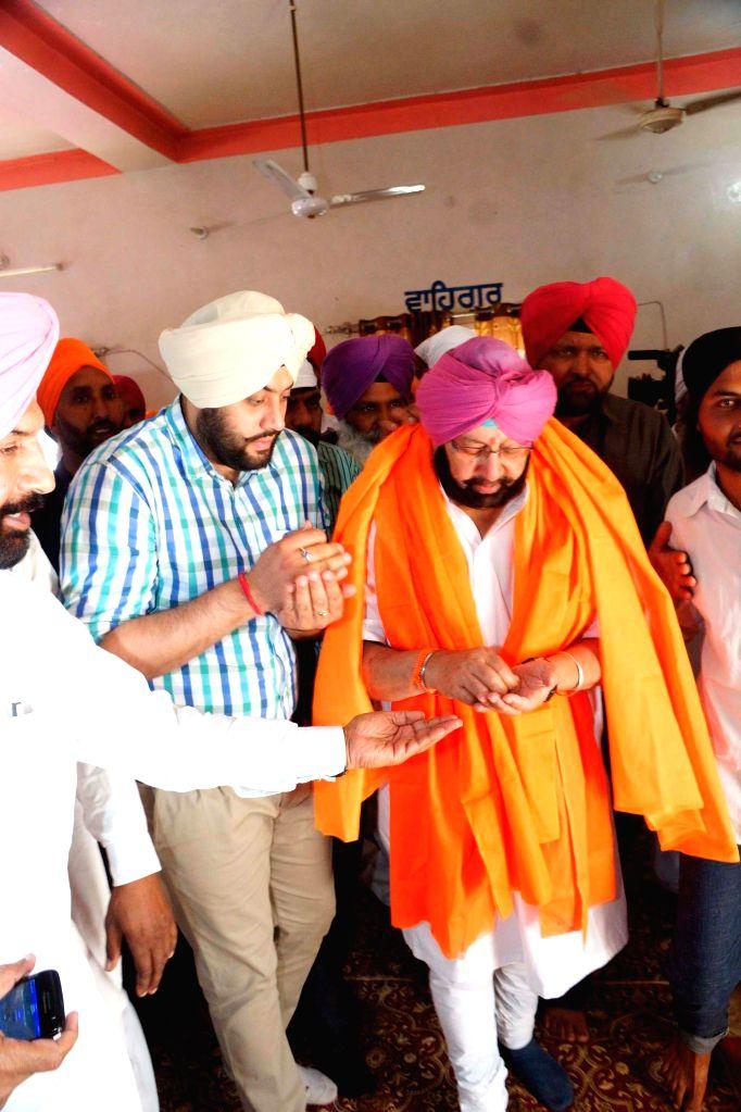 Congress candidate from Amritsar Capt Amarinder Singh paying obeisance at Baba Gum Chuk Ajnala near Amritsar on April 17, 2014.