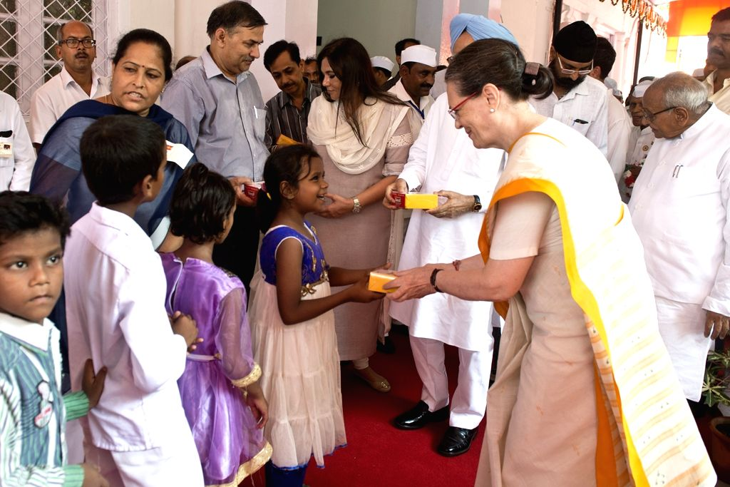Congress chief Sonia Gandhi, vice president Rahul Gandhi and former prime minister and Congress leader Manmohan Singh distribute sweets to children at AICC headquarters on the occasion of ... - Sonia Gandhi, Rahul Gandhi and Manmohan Singh