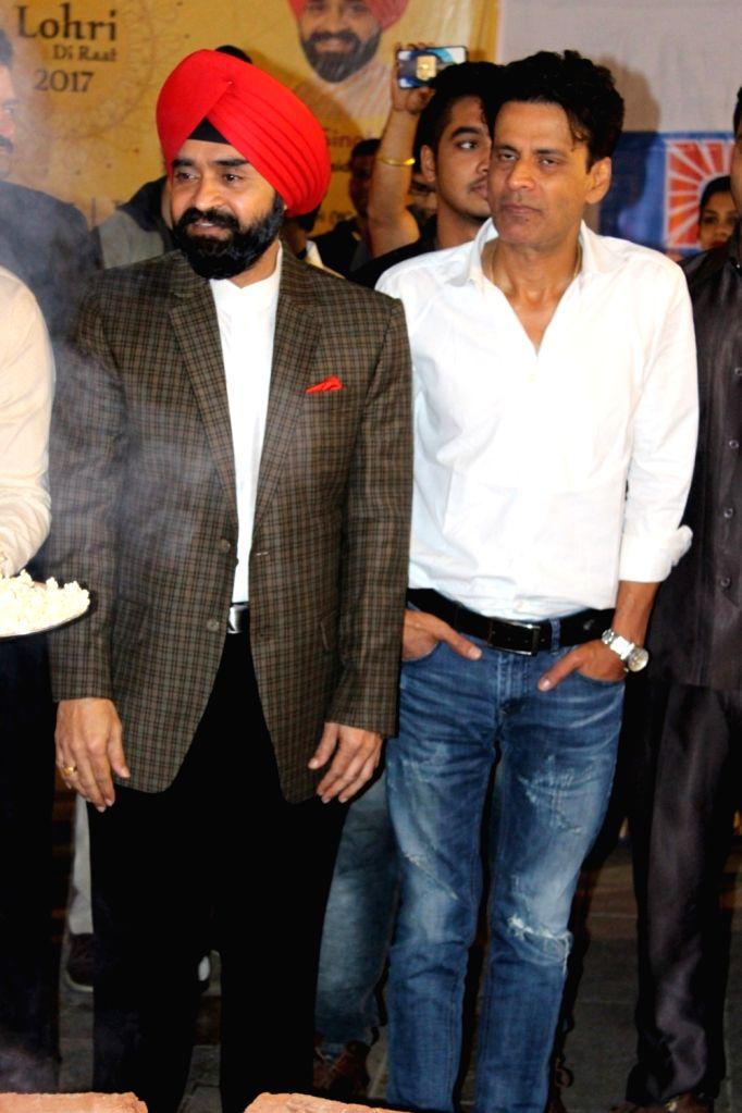 Congress leader Charan Singh Sapra and actor Manoj Bajpayee during the Lohri festival celebration in Mumbai on Jan 12, 2017. - Manoj Bajpayee and Charan Singh Sapra