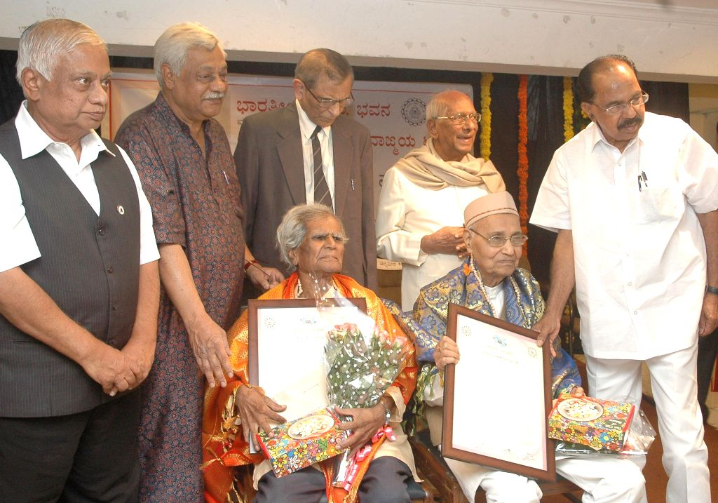 Congress leader M Veerappa Moily felicitates Prof. V K Gokak and Dr. G S Amura during a programme in Bangalore on Sept 7, 2014.