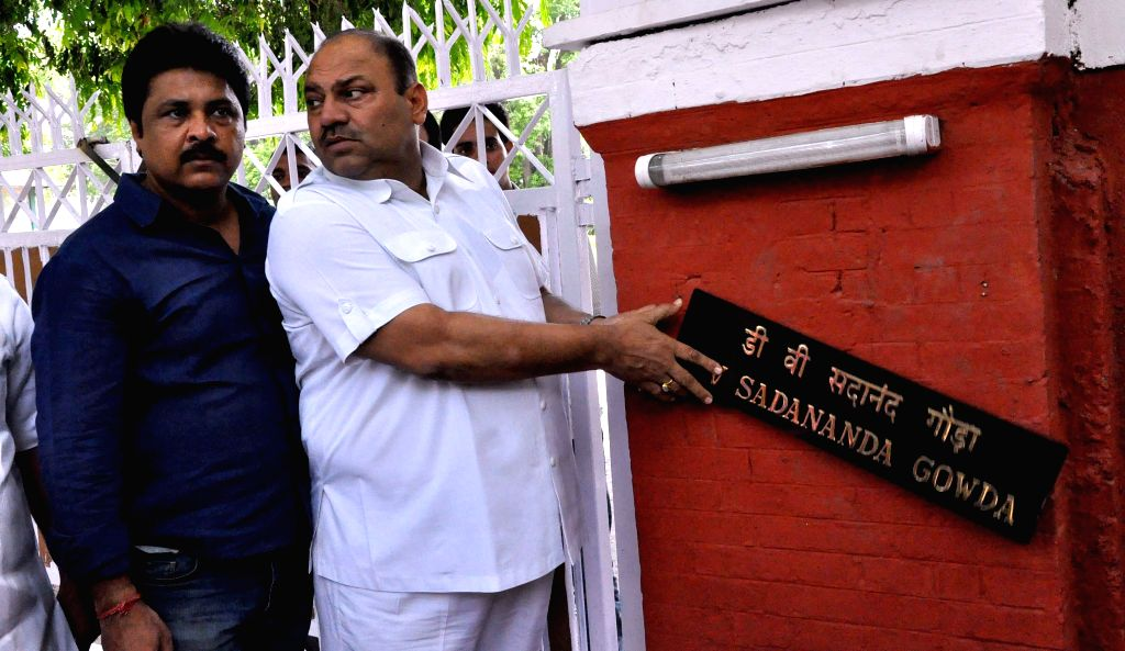 Congress leader Mukesh Sharma remove the name plate of Union Railway Minister D.V. Sadananda Gowda placed outside his residence as they demonstrate against Rail budget 2014-15 in New Delhi on July 8, - D. and Mukesh Sharma
