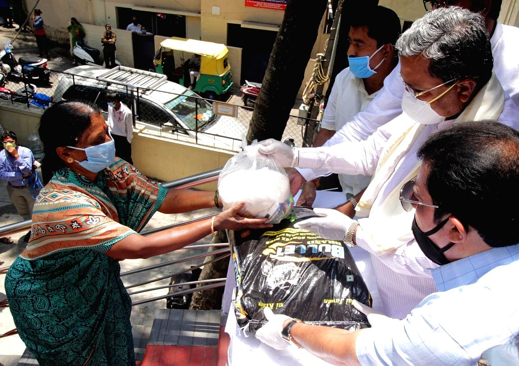Congress leader Siddaramaiah along with MLA Zameer Ahmed Khan distributes free ration kits to poor people at Chamarajpet during the extended nationwide lockdown imposed to mitigate the ... - Zameer Ahmed Khan