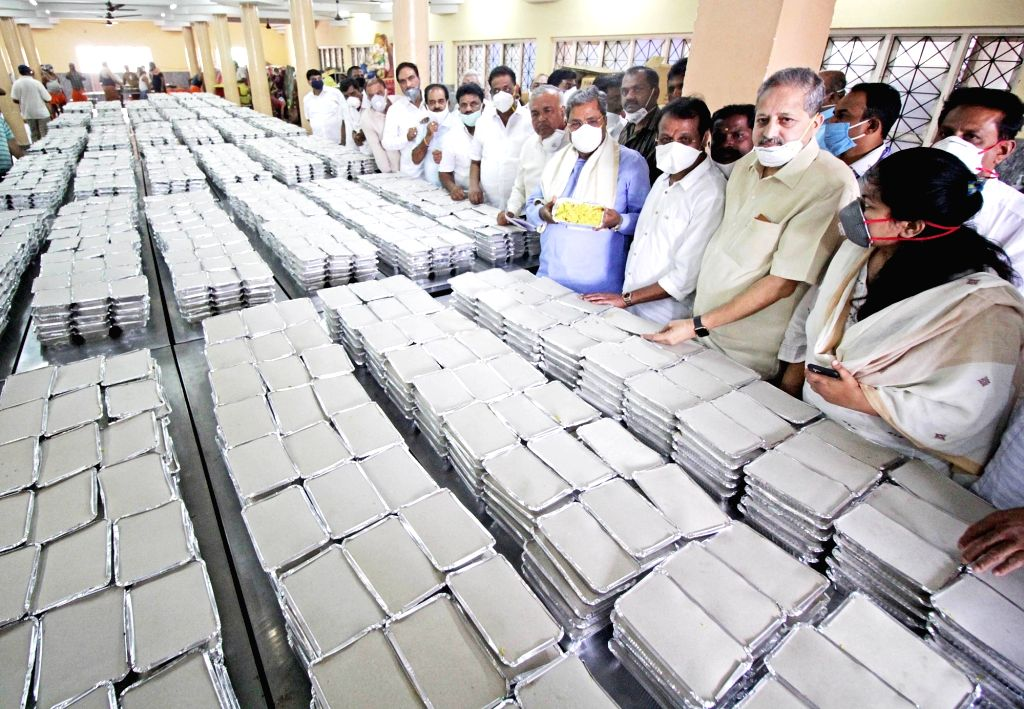 Congress leader Siddaramaiah inspects food packets prepared to be distributed among the poor, needy and homeless people in Bengaluru  during the extended nationwide lockdown imposed to ...