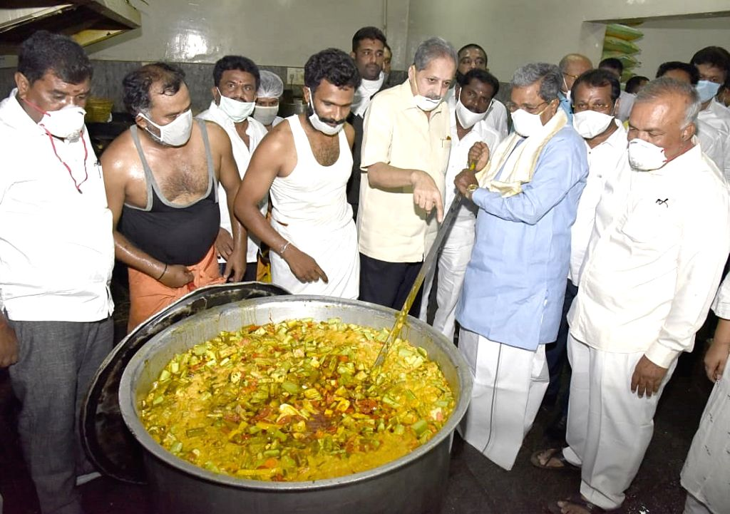 Congress leader Siddaramaiah inspects the food being prepared to be distributed among the poor, needy and homeless people in Bengaluru  during the extended nationwide lockdown imposed to ...