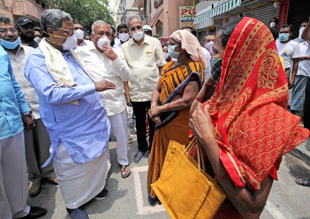 Congress leader Siddaramaiah interacts wth lovcals on his arrival to inspect the food being prepared to be distributed among the poor, needy and homeless people in Bengaluru  during the ...