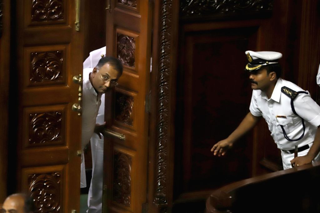 Congress legislator Dinesh Gundu Rao peeps inside Karnataka Assembly where Chief Minister HD Kumaraswamy moved motion of confidence in Bengaluru on July 18, 2019. - Dinesh Gundu Rao