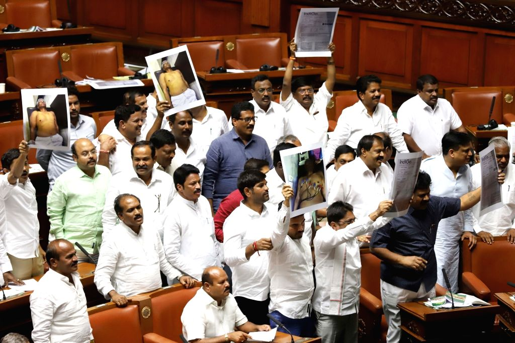 Congress legislators stage a protest holding  photographs of Shrimant Patil who us is hospitalised, in Karnataka Assembly where Chief Minister HD Kumaraswamy moved motion of confidence in ... - Shrimant Patil