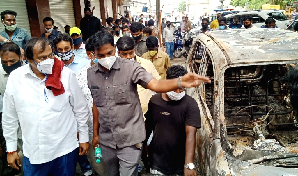 Congress MLA Akanda Srinivas Murthy visits his residence that was set on fire by an irate mob during violence that erupted overnight on Tuesday in Devara Jeevanahalli and Kadugondanahalli ...