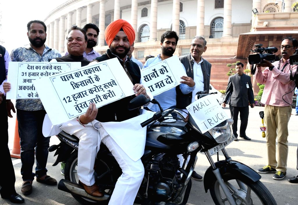 Congress MP's Ravneet Bittu and Santokh Choudhry ride a bike to protest against Rs 31000 cr wheat scam in Punjab at Parliament in New Delhi on Nov 24, 2016.