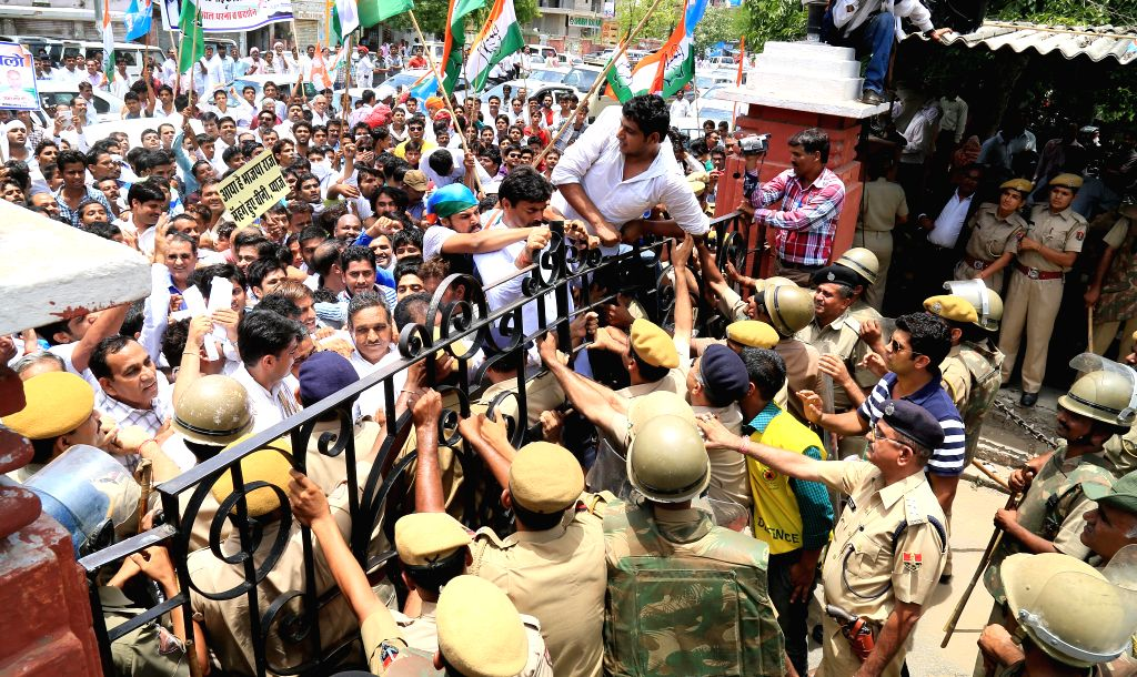 Congress workers demonstrating against hike in prices of essential commodities try to jump the gates of the collectorate when police stopped them from entering premises in Jaipur on July 9, 2014.
