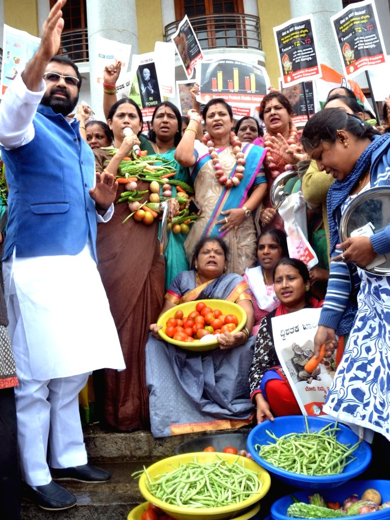 Congress workers stage a demonstration against hike in prices vegetables in Bengaluru on June 29, 2016.