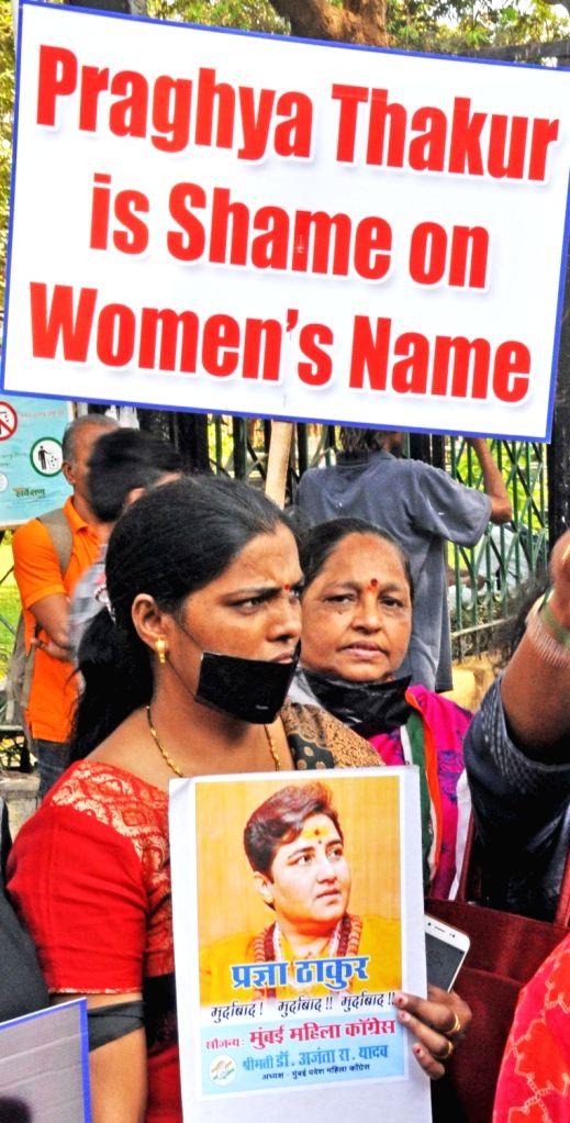 Congress workers stage a demonstration against BJP's Lok Sabha candidate from Bhopal Sadhvi Pragya Singh Thakur over her remark describing Mahatma Gandhi's assassin Nathuram Godse as a ... - Nathuram Godse