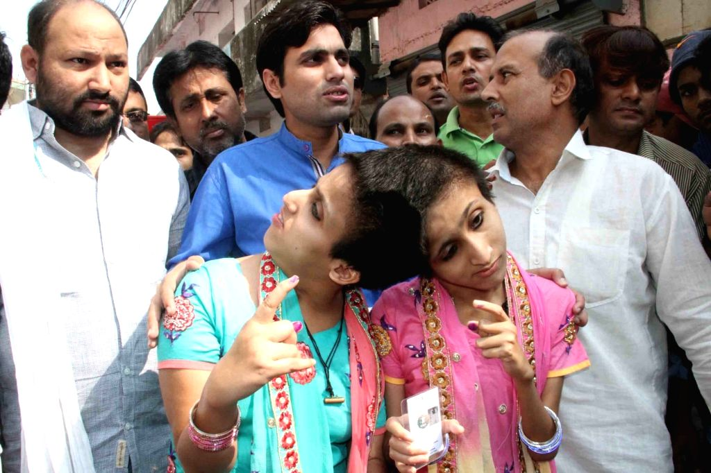 Conjoined twins Saba and Farah show their finger marked with phosphorous ink after casting their vote during the third phase of Bihar assembly polls in Patna on Oct 28, 2015.
