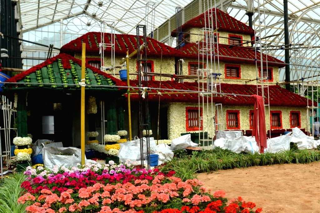"Construction of the floral replica of Kannada poet Rashtrakavi Kuvempu's house ""Kavishala"" using Dutch White and Red roses underway ahead of the upcoming Independence Day Flower Show ..."