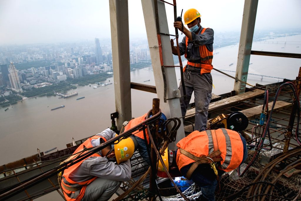 Constructors work at a height of about 500 meters at the construction site of a high rise building in Wuhan, central China's Hubei Province, Aug. 11, 2020. The ...