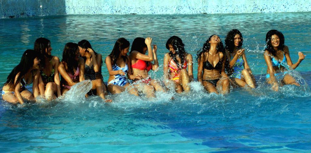 "Contestants pose for photographers during the swimwear round of ""Dabur Gulabari Sananda Tilottama"" on Wednesday in Vedic Village of Kolkata on 10 Jun 2009. Ten finalists were present for the"