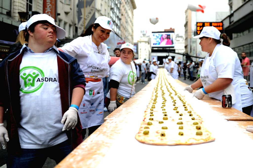 Cooks prepare a 60-meter-long pizza on Corrientes Avenue in Buenos Aires, capital of Argentina, on Nov. 1, 2015. According to local press, at least a dozen of ...