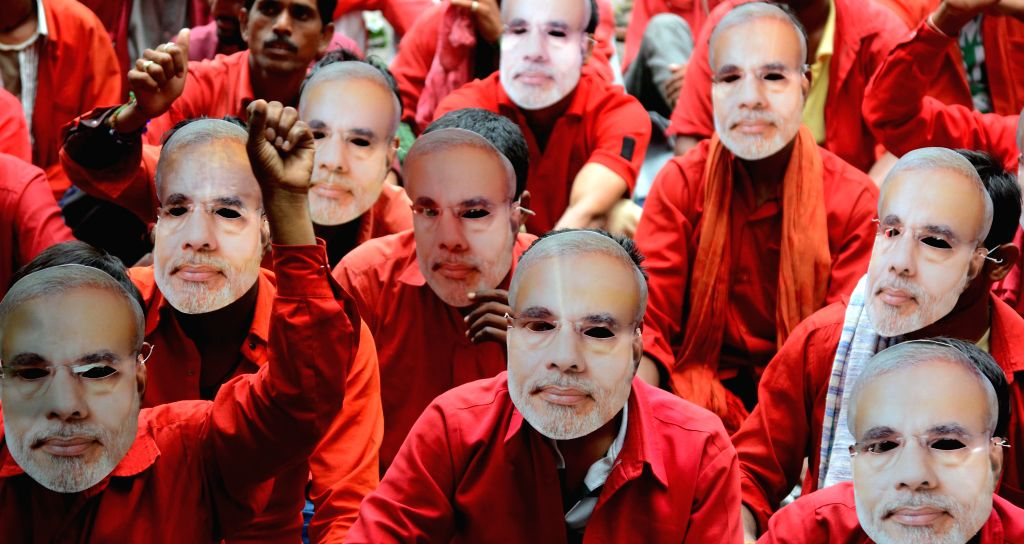 Coolies wearing masks of Prime Minister Narendra Modi stage a demonstration at Jantar Mantar to demand regularisation of their jobs in New Delhi on Sept 11, 2014. - Narendra Modi